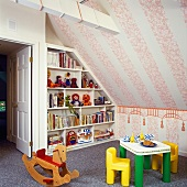 Corner of child's attic bedroom with books and toys on shelving, children's furniture and wooden rocking horse