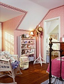 Ornaments on white shelves in child's bedroom with pink wallpaper and white wicker rocking chair