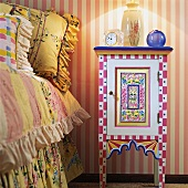 Hand-painted, colourful bedside cabinet next to child's bed with pretty cushions and ruffled bedspread; pink and white striped wallpaper