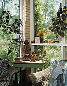 Corner of glazed veranda in the country with vintage table, wicker chairs and terracotta ornaments
