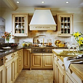Nostalgic country-house kitchen with light wooden furniture and chimney-breast-style extractor hood