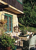 Sun terrace of stone house comfortably furnished with vintage furniture and potted plants