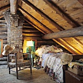 Rustic attic bedroom with old beamed ceiling, wood and brick wall and patterned cushions and blankets on a single bed