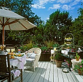 Wicker armchair and many potted plants on sunny wooden terrace with parasol and laid dining table