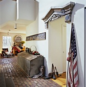 Hallway with terracotta tiles and doorway with wooden frieze decorated with antiques and flags from the American Civil War