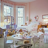 Child's bedroom in pink and light blue with ornate bed and children's furniture with dolls and soft toys