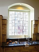 Arched, leaded glass kitchen window above sink in marble worksurface