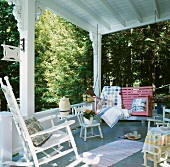 White wooden veranda in the country with white rocking chair, pink porch swing and children's' chairs