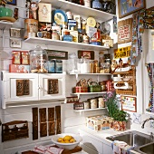 Shelving on kitchen wall holding large collection of tin cans and curiosities: small kitchen cupboard decorated with old wooden moulds