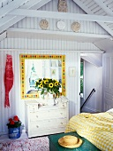 Mirror with colourful frame, yellow and white bedspread and children's handprints on shelf in gable of roof in sunny bedroom