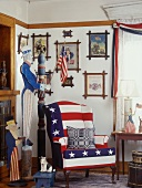 American room with whimsical Uncle Sam figure, stars and stripes armchair and collection of pictures on wall