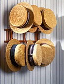 Twenties-style straw hats hanging on wooden hat pegs