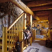 Rustic log cabin with stone wall, staircase and view into dining area