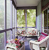 Glazed, sunny veranda with decorative gingham and floral cushions on porch swing and wicker furniture