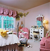 Charming child's bedroom in shades of pink with playful dressing table and whimsical mural
