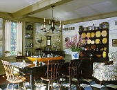 Dark furniture characterise a dining room with a collection of crockery, stoneware, pewter and knickknacks