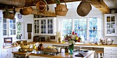 Bright, country-house kitchen with island and baskets hanging from beamed ceiling