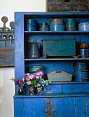 Blue, vintage-style kitchen dresser holding collection of blue kitchen utensils and three posies of summer flowers