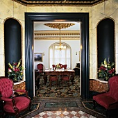Polygonal hall with marble tiled floor, bouquets in niches, brocade armchairs and view into fine dining room