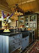 Rustic, cosy kitchen with rug and ceiling-height kitchen dresser
