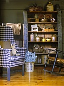 Vintage-style wooden shelving holding collection of antiques next to armchair with blue and white gingham upholstery and rocking chair