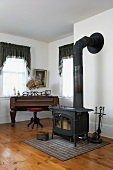 Black wood-burning stove next to antique piano and swivel stool