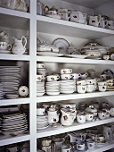 White shelving with large collection of fine china