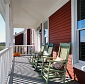 Row of rocking chairs on sunny, roofed veranda of wooden house