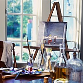 Painting on easel and painting utensils in front of lattice window