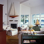 Large windows and large model sailing boat above open fireplace in living room
