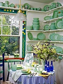 An extensive collection of Fire King crockery in pastel green in the corner of kitchen with a sash window and a round table