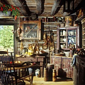 Kitchen in rustic log cabin with wood-beamed ceiling and antique kitchen utensils
