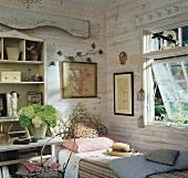Ländlicher Raum mit Holzwänden, einem Einzelbett mit kunstvollem Kopfende und einem weissen Hortensienstrauss