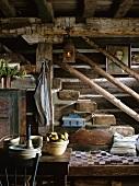 Rustikales Treppenhaus mit alten Deckenbalken, einer antiken Laterne und einer rustikalen Holzsitzbank