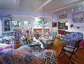 Interior with open balcony door, furniture upholstered in various pastel patterns and serving hatch to kitchen