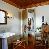 Simple bathroom with pedestal washbasin and antique furnishings