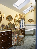 Ornate attic bathroom with free-standing bathtub and gilt-framed, fan-shaped pictures on walls