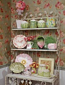 Collection of unusual crockery on artistic shabby chic metal shelving against rose-patterned wallpaper
