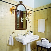Antique bathroom with pedestal washstand, cream wall and floor tiles and flowering orchid