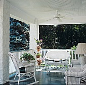 Roofed veranda with ceiling fan, white wicker furniture and table lamp with wicker base