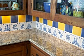 Detail of kitchen corner with granite worksurface and decorative wall tiles in blue and yellow above row of original, unique tiles with blue patterns