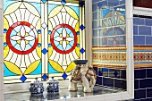 Stained and leaded glass window in Victorian bathroom with reflective wall tiles