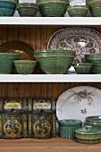 Antique crockery and an antique tin on a shelf