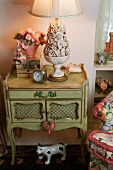 Antique bedside table with ceramic bowl of flowers as lamp base