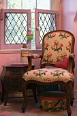 Armchair with rose-patterned upholstery in pink room
