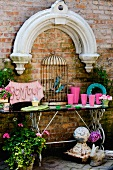 Brick wall decorated with stone arch and birdcage