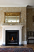 Traditional living room with open fireplace below mirror on wall with stencilled patterns