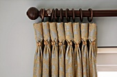 Dark wood curtain pole and gathered curtain with decorative metal buttons