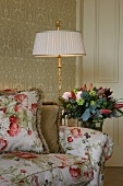 Floral sofa with cushions in same fabric next to standard lamp and bouquet in semi-darkness