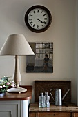 Simple table lamp on kitchen base unit and antique clock on wall above old wooden table